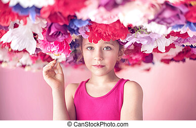 Cute little girl among colorful flowers