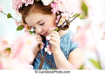 Cute little girl among flowers