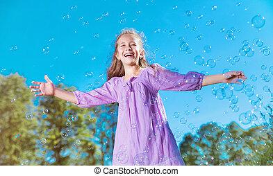 Cute little girl among lots of soap bubbles