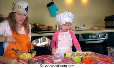 Cute little girl and beautiful mom in aprons are playing while kneading dough