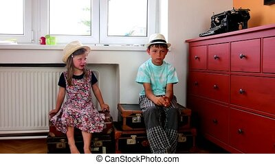 Cute little girl and boy sit on vintage suitcases and wait on starting holiday. Smalll girl wears flowered dress. Travelling concept
