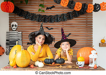Cute little girl and her mother sitting behind a table in Halloween theme decorated room, looking at camera with hand on chin and smiling. Family Halloween lifestyle.
