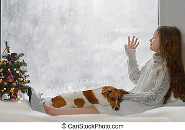Cute little girl and her puppy jack russell sitting by the window