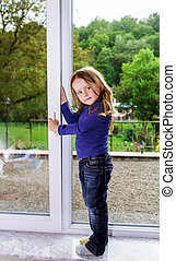 Cute little girl and pvc window