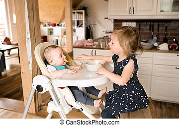 Cute little girl at home feeding her baby brother.