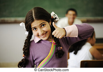 Cute little girl at school with thumb up