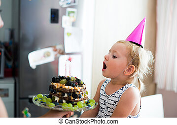 Cute little girl blowing candles on her birthday cake