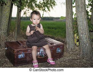 Cute little girl blowing dandelion on a suitcase outside