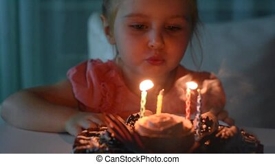 cute little girl blowing out candles on birthday cake