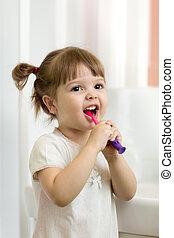 Cute little girl brushing teeth in bathroom