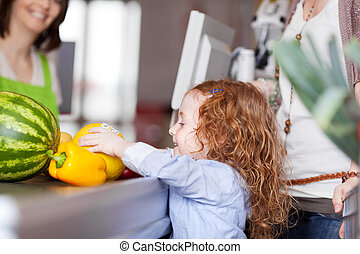 Cute little girl buying groceries placing the fresh fruit on...