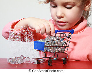 Cute little girl care play with toy shopping trolley filled by small balls
