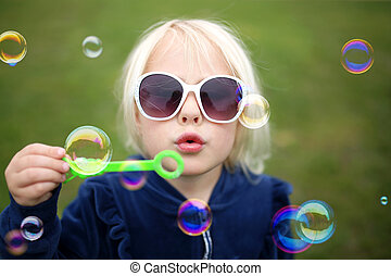 Cute Little Girl Child Blowing Bubbles Outside on a Summer Day