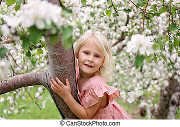 Cute Little Girl Child Playing OUtside in Spring Orchard on Apple Tree