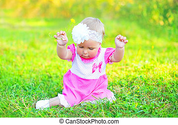 Cute little girl child with yellow flower sitting on grass in summer day