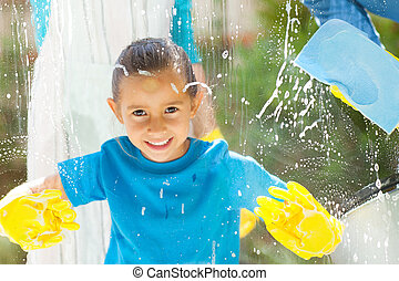 cute little girl cleaning window glass with parents