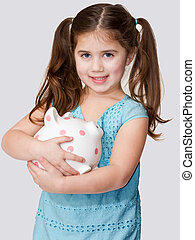 Cute little girl cradles a pink polka dotted piggybank in arms.