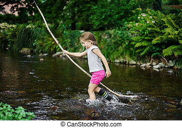 Cute little girl crossing river with cane
