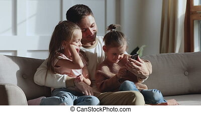 Cute little girl daughter learning using smartphone relaxing with family