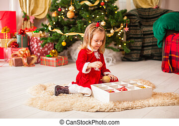Cute little girl decorating a Christmas tree with colorful baubles at home