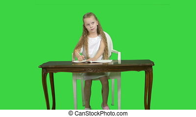 Cute little girl doing homework, writing down on a Green Screen, Chroma Key