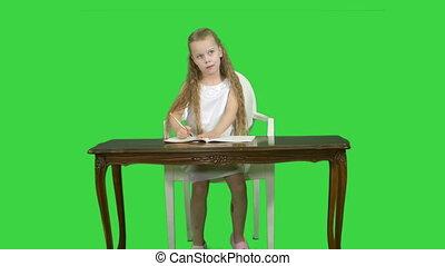 Cute little girl doing homework, writing down on a Green Screen, Chroma Key
