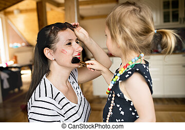 Cute little girl doing make-up to her attractive mom with brush.