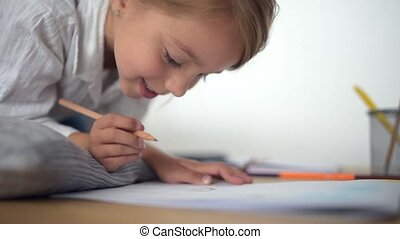 Cute little girl drawing at the table