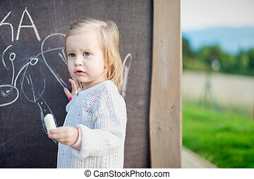 Cute little girl drawing on blackboard. Toddler girl having fun outdoors, holding chalk and drawing.