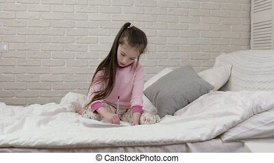 cute little girl drawing pictures while lying on bed. Kid...