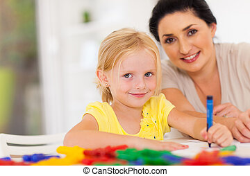 cute little girl drawing with mother