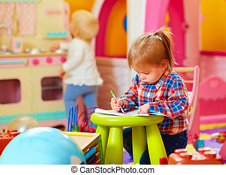 cute little girl drawing with pencil in kindergarten