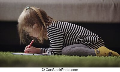 Cute little girl drawing with pencil in nursery. Small princess is playing by painting the pattern with red pen. Blonde child crayoning the picture on the floor with the bed in the background.