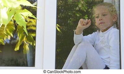 Cute little girl draws a finger on  window pane
