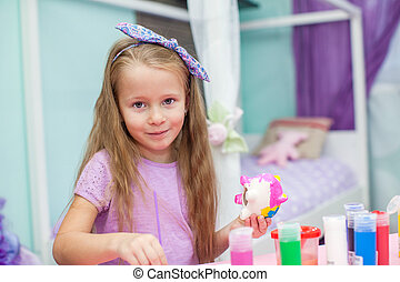 Cute Little girl draws paints at her table in the room
