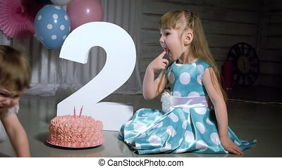 Cute little girl dressed like princesses eating whipped cream from birthday cake