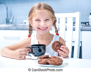cute little girl drinking tea with cookies