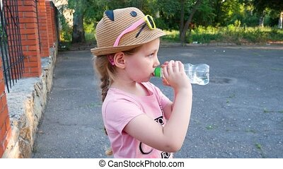 Cute little girl drinking water from bottle outdoor. Child ...
