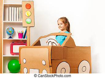 Cute little girl driving her toy cardboard car