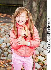 Cute little girl eating a snack after school outdoors