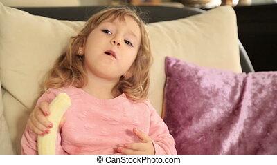 Cute little girl eating banana