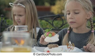 Cute little girl eating cake in the open air cafe