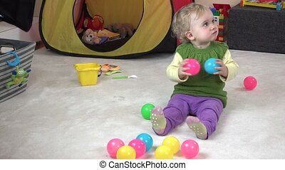 cute little girl eating crackers and playing with colorful balls.