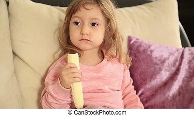 Cute little girl eating  eating a banana