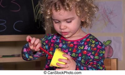 cute little girl eating her favorite yogurt with spoon. -...