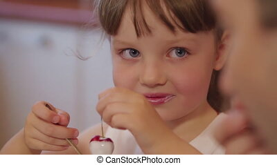 Cute little girl eating ice cream in the kitchen. Daughter holding and examining a cherry in her hand