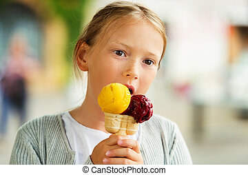 Cute little girl eating ice cream outdoors