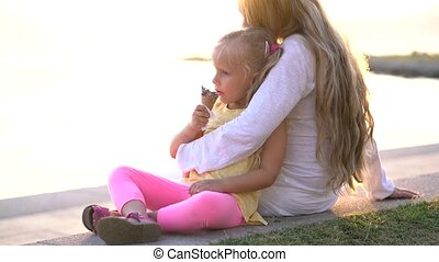 cute little girl eating ice cream while sitting on the promenade in mother's arms