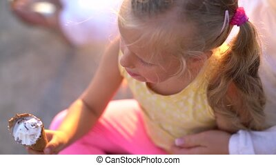 cute little girl eating ice cream while sitting on the...