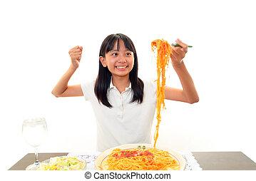 Cute little girl eating spaghetti